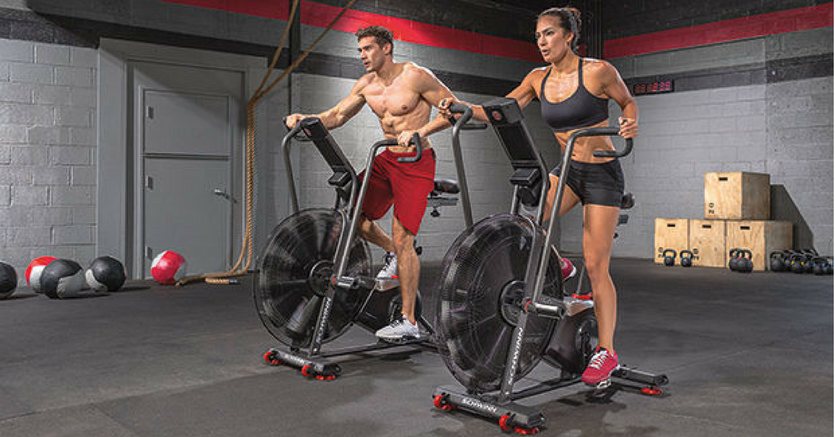 Man and woman each riding airdyne spin bike inside gym
