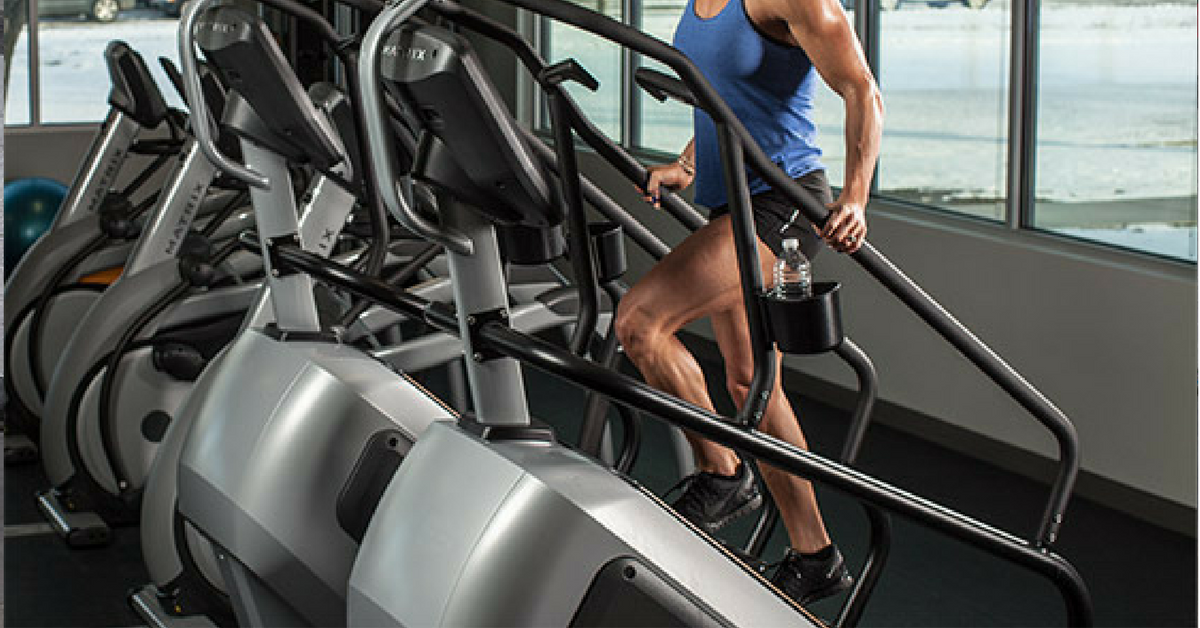 Woman exercising on stair stepper at gym