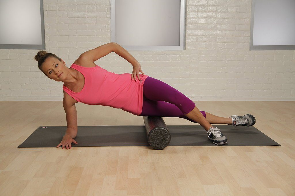 Woman foam rolling IT band