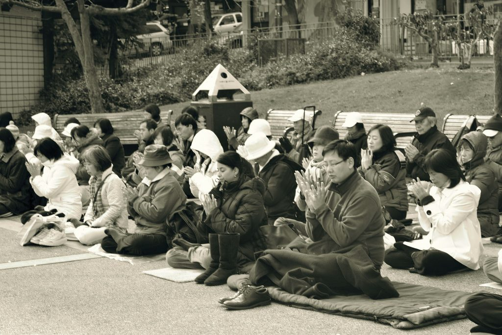 Group of people meditating in public