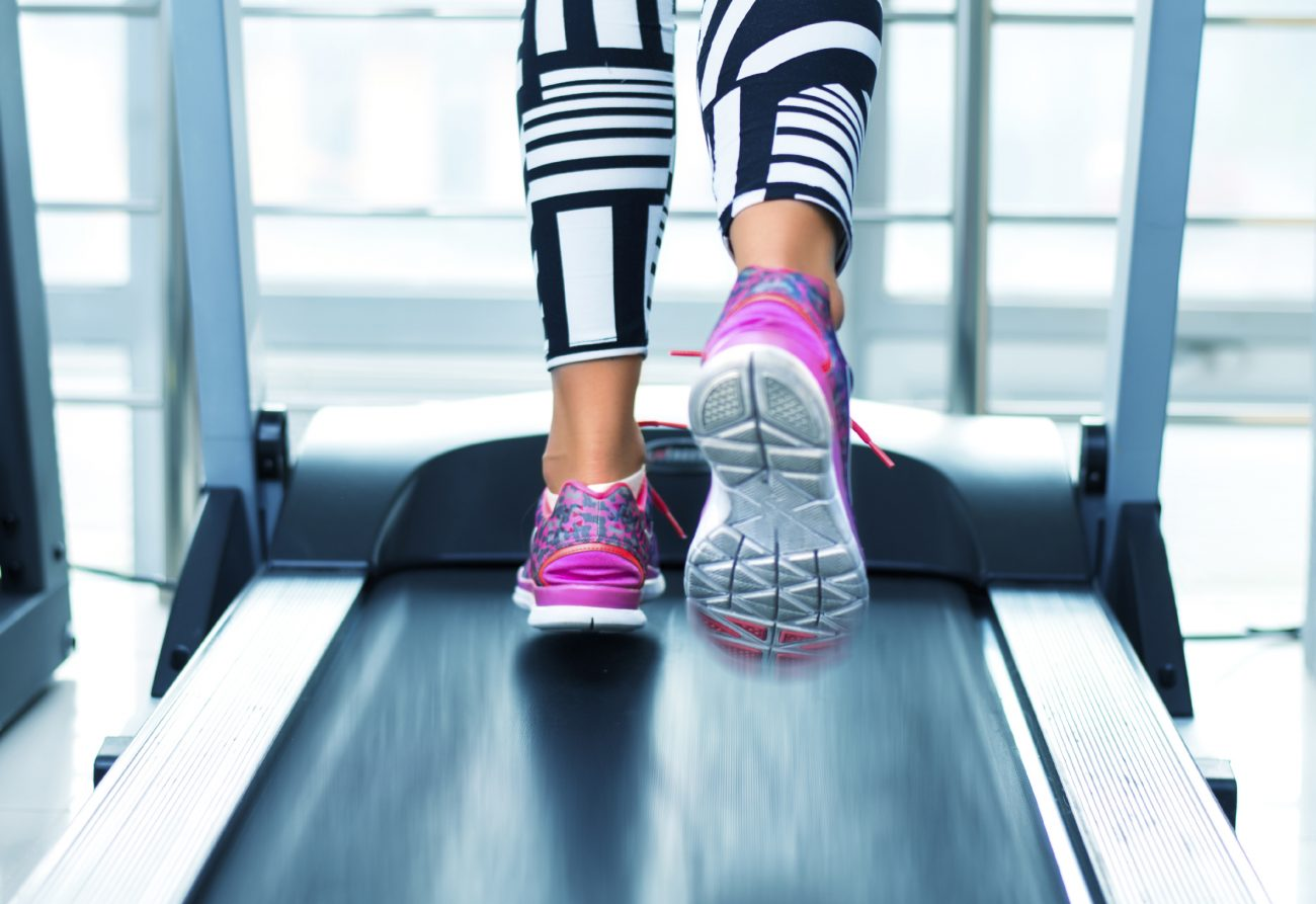 Close up of woman running on treadmill