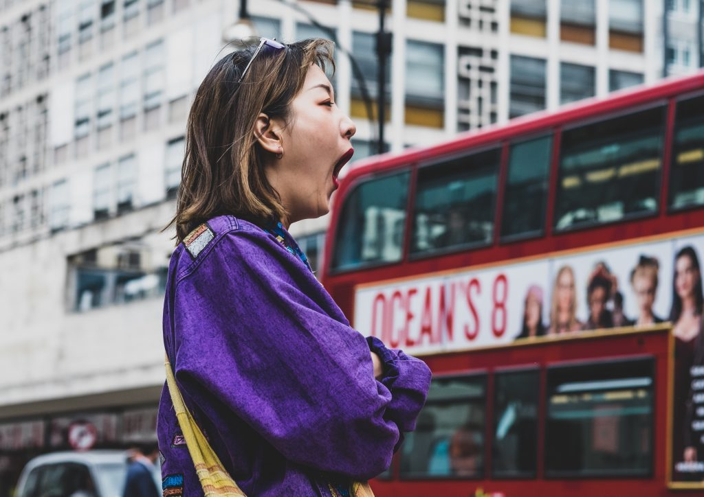 Woman yawning on street